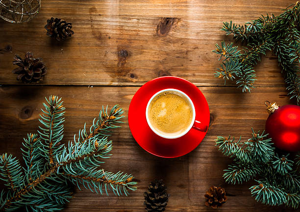 Christmas breakfast, fragrant coffee next to the Christmas tree branches, pine cones and decorations, top view, copy space
